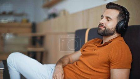 Photo pour Heureux homme dans les écouteurs sans fil refroidissant dans le café - image libre de droit
