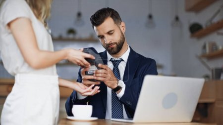 blurred waitress holding credit card reader near businessman in cafe