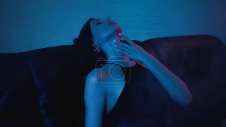 red lighting on face of seductive brunette woman touching neck on blue with smoke