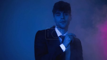 Photo for Man in suit looking at camera on blue with smoke - Royalty Free Image