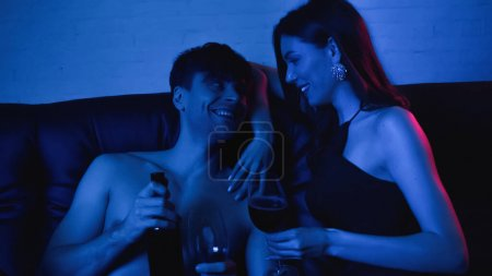 Photo for Happy and shirtless man holding bottle with wine near sexy girlfriend on blue - Royalty Free Image