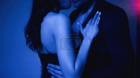 Photo for Cropped view of woman hugging man in blazer on blue - Royalty Free Image
