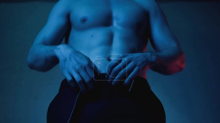 cropped view of sexy and muscular man undressing on blue