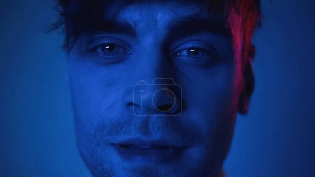 Photo for Close up of man looking at camera on blue - Royalty Free Image