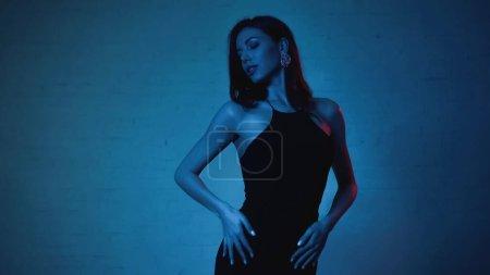 Photo for Elegant woman in black slip dress posing on blue background - Royalty Free Image