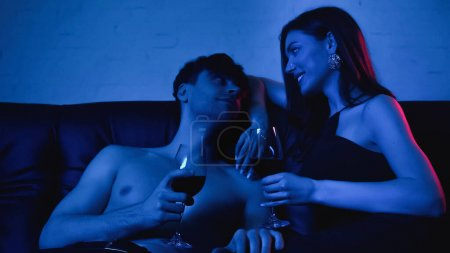 sexy couple holding glasses of wine and smiling while looking at each other on blue