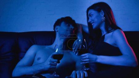 Photo pour Couple sexy tenant des verres de vin et souriant tout en se regardant sur bleu - image libre de droit