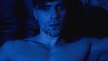 Photo for Blue lighting on shirtless man looking at camera - Royalty Free Image
