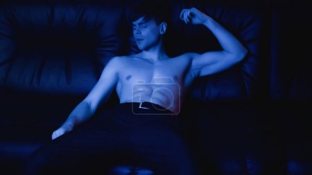 Photo for Shirtless man in pants relaxing on black sofa on blue - Royalty Free Image