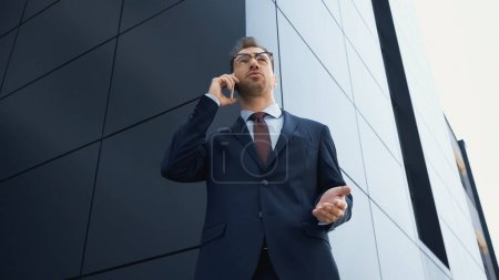 Photo for Low angle view of businessman in suit and glasses talking on smartphone outside - Royalty Free Image