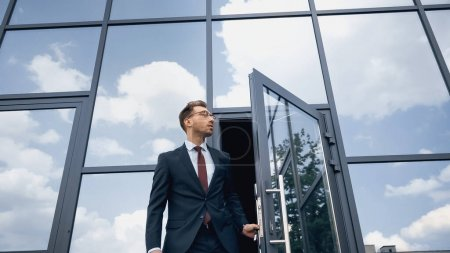 low angle view of man in suit and glasses opening door while walking outside
