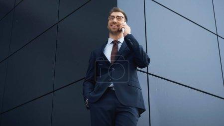 Photo pour Vue à angle bas de l'homme d'affaires heureux en costume et lunettes parlant sur smartphone à l'extérieur - image libre de droit