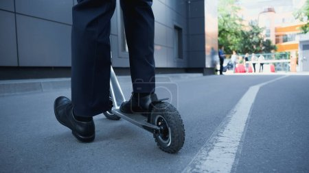 Photo for Partial view of businessman in suit riding electric scooter outside - Royalty Free Image