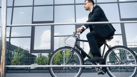 full length of businessman in suit and glasses riding bike near building with glass facade