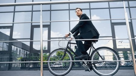 Photo for Full length of businessman in suit riding bicycle near building with glass facade - Royalty Free Image