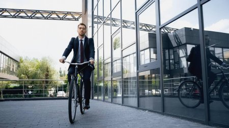Photo for Full length of businessman in suit riding bicycle near building - Royalty Free Image