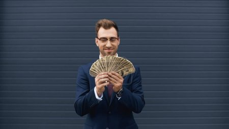 cheerful businessman in suit smiling while holding dollars