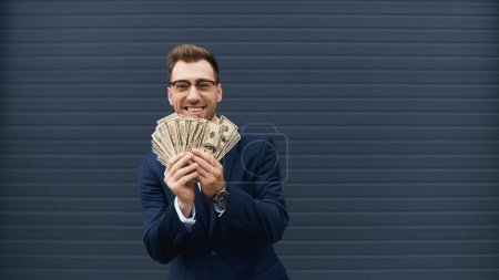 rich businessman in suit smiling while holding dollars