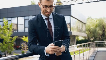 Photo for Happy businessman in glasses and suit using smartphone - Royalty Free Image