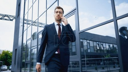 confident businessman in glasses and suit talking on smartphone while walking near building