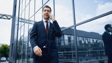 Geschäftsmann in Brille und Anzug spricht auf Smartphone, während er in der Nähe eines Gebäudes spaziert