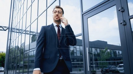 cheerful businessman in glasses and suit talking on smartphone while walking near building