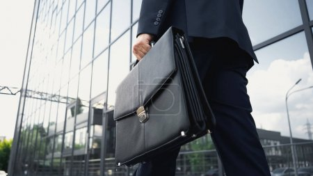 cropped view of businessman walking with leather briefcase
