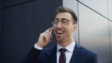 Photo pour Homme d'affaires heureux en lunettes et costume parler sur téléphone mobile près de l'immeuble - image libre de droit