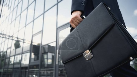 cropped view of businessman holding leather briefcase