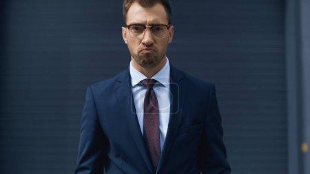 Photo pour Bouleversé homme d'affaires dans des lunettes regardant la caméra - image libre de droit