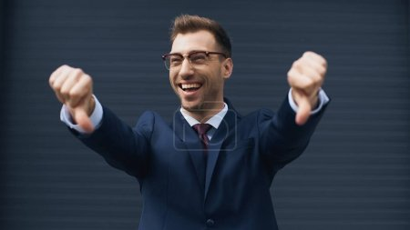 cheerful businessman in glasses showing thumbs down