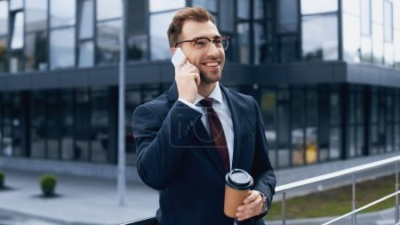 Photo for Happy businessman talking on mobile phone and holding coffee to go outside - Royalty Free Image