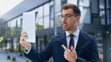 Photo for Businessman in glasses having video call while holding digital tablet outside - Royalty Free Image
