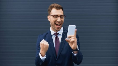Photo for Excited businessman in glasses and formal wear holding cellphone outside - Royalty Free Image