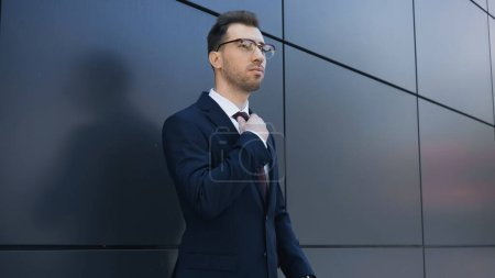 businessman in glasses adjusting tie near building