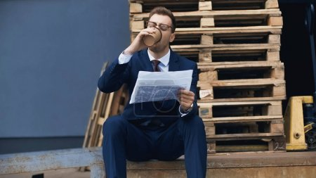 Photo for Businessman sitting while drinking coffee to go and reading newspaper outside - Royalty Free Image