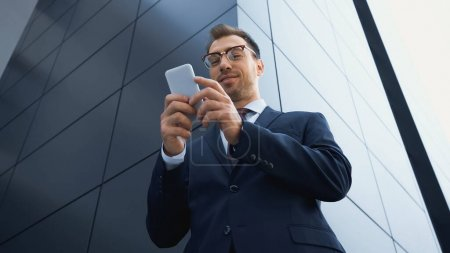 Photo for Low angle view of pleased businessman in glasses texting on mobile phone outside - Royalty Free Image