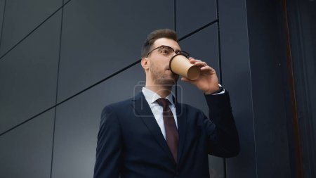 Photo for Businessman drinking coffee to go outside - Royalty Free Image