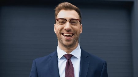 Photo for Positive businessman in formal wear and glasses laughing while looking at camera - Royalty Free Image
