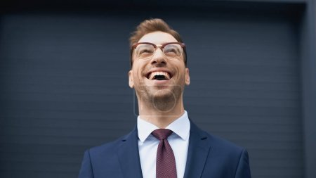 positive businessman in formal wear and glasses laughing while looking up