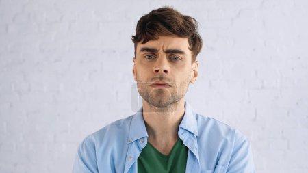 Photo pour Mécontent homme en chemise floue regardant la caméra - image libre de droit