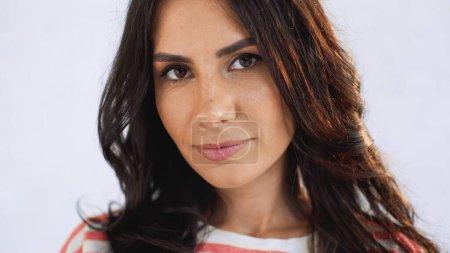 Photo pour Gros plan de la femme brune regardant la caméra près du mur de briques blanches - image libre de droit