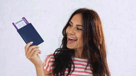 Photo for Smiling woman looking at passport with air ticket - Royalty Free Image