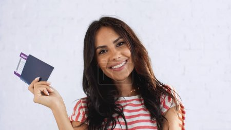 joyful woman holding passport with air ticket while looking at camera