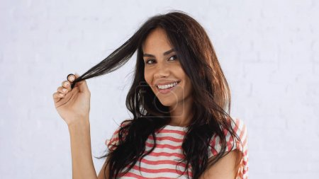 Photo for Cheerful woman touching brunette hair and looking at camera - Royalty Free Image