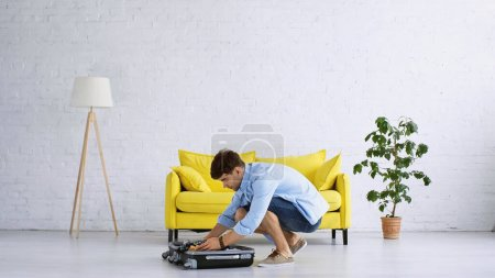 man in blue shirt packing baggage in modern living room