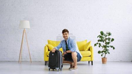 Photo pour Homme heureux en chemise bleue assis près des bagages dans le salon - image libre de droit