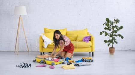 brunette woman packing suitcase near summer clothes on floor in living room
