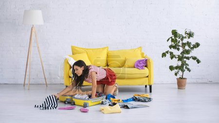 Photo for Brunette woman packing luggage with summer clothes on floor in living room - Royalty Free Image