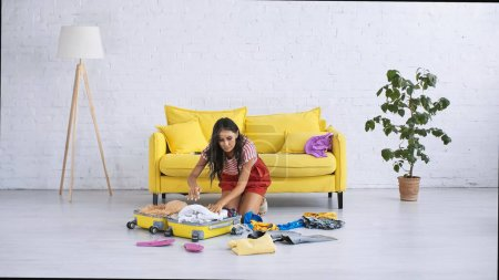 Photo for Brunette woman packing baggage with summer clothes on floor in living room - Royalty Free Image